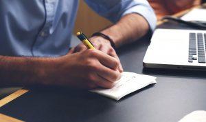 Mężczyzna piszący na kartce papieru przy komputerze