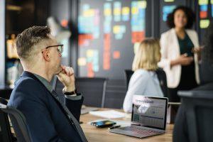 Mężczyzn siedzący przed komputerem obok dwóch kobiet