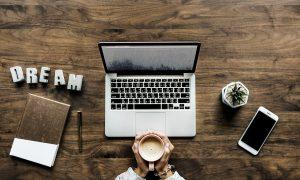 Człowiek trzymający kawę, siedzący przy komputerze i smartphonie