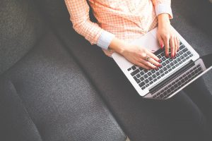 Blogerka trzymająca laptopa na kolanach
